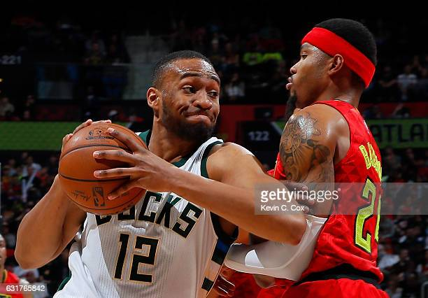Kent Bazemore of the Atlanta Hawks draws a charge from Jabari Parker of the Milwaukee Bucks at Philips Arena on January 15 2017 in Atlanta Georgia...