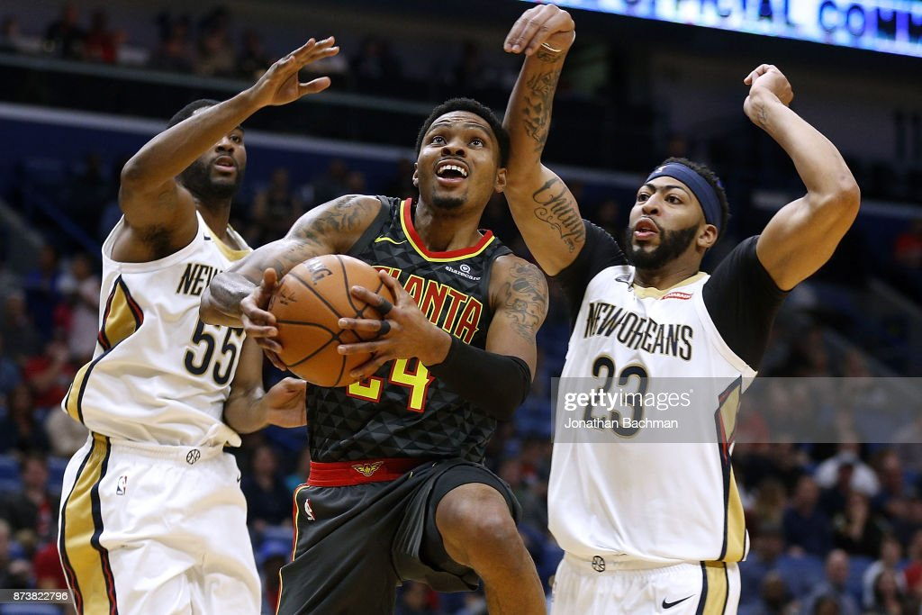 Kent Bazemore #24 of the Atlanta Hawks drives between Anthony Davis #23 of the New Orleans Pelicans and E'Twaun Moore #55 during the first half of a game at the Smoothie King Center on November 13, 2017 in New Orleans, Louisiana.
