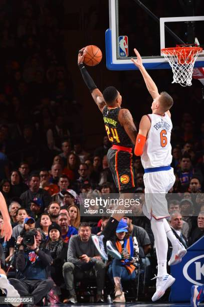 Kent Bazemore of the Atlanta Hawks goes up for the dunk against Kristaps Porzingis of the New York Knicks at Madison Square Garden on December 10...