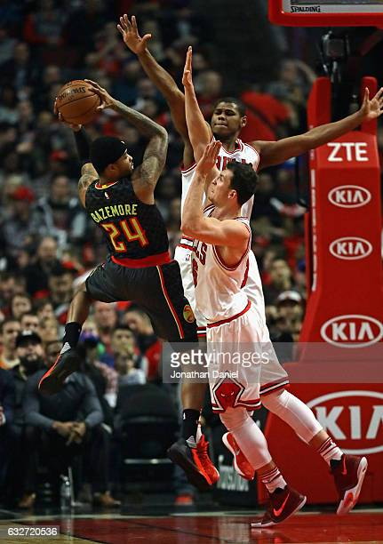 Kent Bazemore of the Atlanta Hawks tries to get off a shot against Paul Zipster and Cristiano Felicio of the Chicago Bulls at the United Center on...