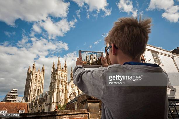 UK, Kent, Canterbury, boy photographing Canterbury Cathedral with his digital tablet