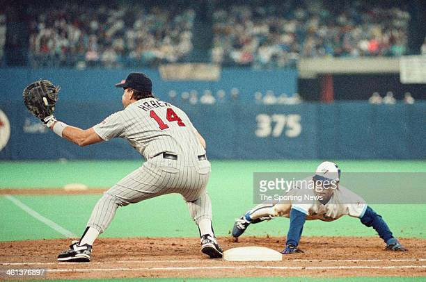 Kent Hrbek of the Minnesota Twins attempts to tag out Roberto Alomar of the Toronto Blue Jays during the 1991 American League Championship Series at...