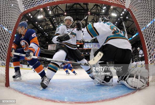 Kent Huskins and Evgeni Nabokov of the San Jose Sharks defend the net against the New York Islanders at the Nassau Coliseum on October 17 2009 in...