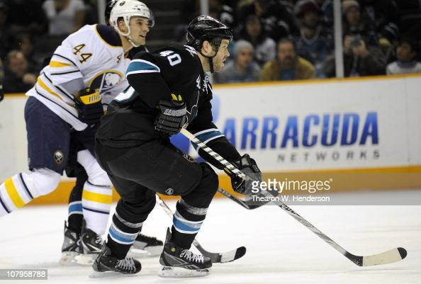 Kent Huskins of the San Jose Sharks skates up ice against Andrej Sekera of the Buffalo Sabres during an NHL hockey game at the HP Pavilion on January...