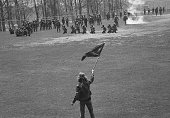 Kent State University student Alan Canfora waves a black flag as Ohio Amry National Guardsmen kneel and aim their rifles on a football field Kent...