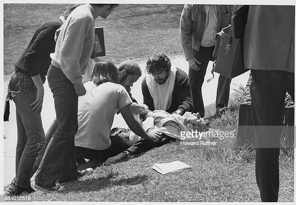 Kent State University student Joe Cullum and others kneel on the grass beside wounded fellow student John Clearly after the latter had been shot when...