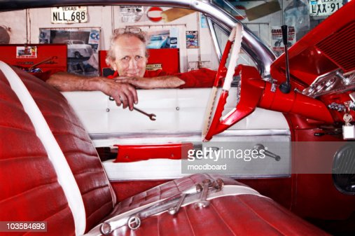 Kent,  UK,  portrait of mechanic in garage leaning over car window : Stock Photo