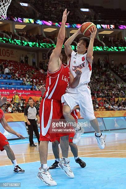 Kenta Hirose of Japan goes up for a shot over Asghar Kardoustpoustinsar of Iran in the second half during the men's bronze medal basketball game at...
