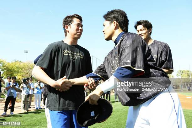 Kenta Maeda of the Los Angeles Dodgers and Takahiro Norimoto of Japan shake hands during a workout ahead of the World Baseball Classic Championship...