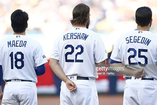 Kenta Maeda Clayton Kershaw and Rob Segedin of the Los Angeles Dodgers observe the playing of the national anthem prior to game three of the National...