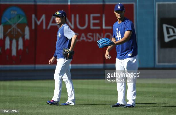 Kenta Maeda left and Yu Darvish of the Los Angeles Dodgers stand in the outfield prior to the MLB game between the San Diego Padres and the Los...