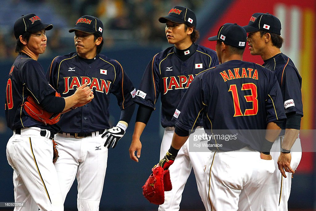 Kenta Maeda #20 of Japan (L) and teammates stand on the mound during the international friendly game between Australia and Japan at Kyocera Dome Osaka on February 24, 2013 in Osaka, Japan.