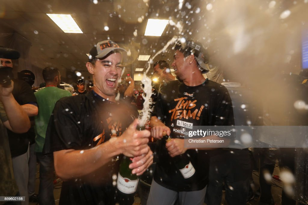 Kenta Maeda #18 of the Los Angeles Dodgers celebrates in the locker room after defeating the Arizona Diamondbacks 3-1 to win game three of the National League Divisional Series at Chase Field on October 9, 2017 in Phoenix, Arizona.
