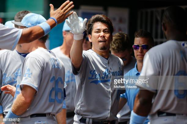Kenta Maeda of the Los Angeles Dodgers high fives teammates after scoring in the second inning against the Cincinnati Reds at Great American Ball...