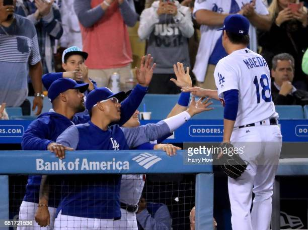 Kenta Maeda of the Los Angeles Dodgers is congratulated by Julio Urias as he leaves the game with a 52 lead during the ninth inning against the...