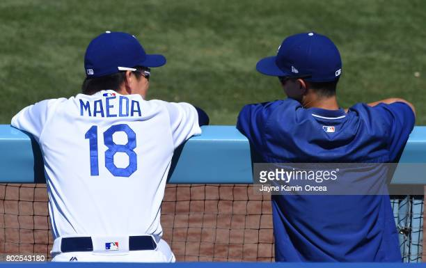 Kenta Maeda of the Los Angeles Dodgers talks with translator Will Ireton as they watch the game against the Colorado Rockies at Dodger Stadium on...