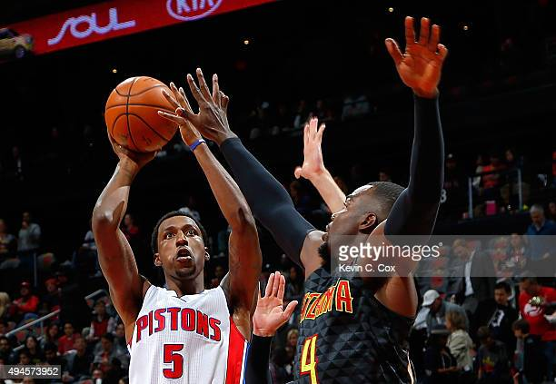 Kentavious CaldwellPope of the Detroit Pistons shoots against Paul Millsap and Kyle Korver of the Atlanta Hawks at Philips Arena on October 27 2015...