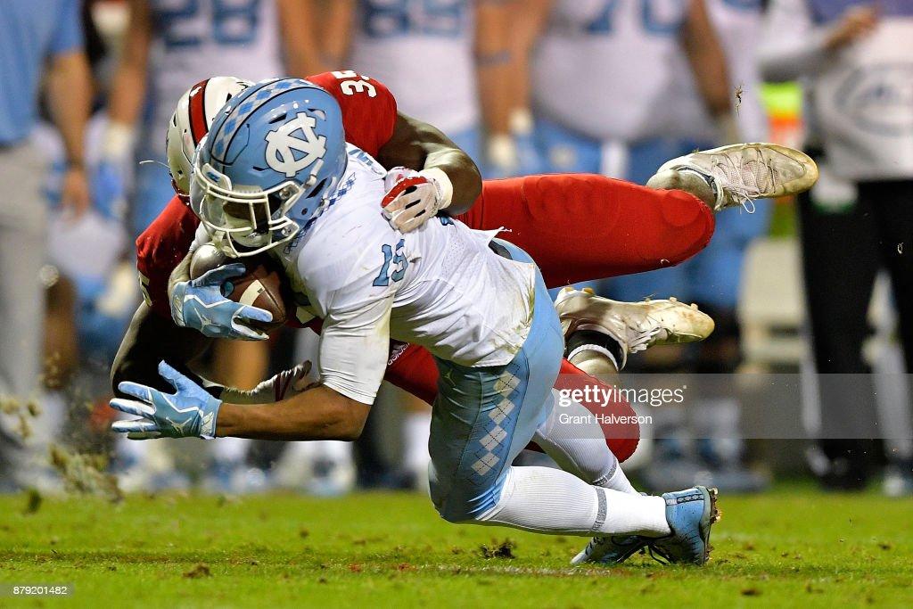 Kentavius Street #35 of the North Carolina State Wolfpack tackles Jack Davidson #15 of the North Carolina Tar Heels during their game at Carter Finley Stadium on November 25, 2017 in Raleigh, North Carolina. North Carolina State won 33-21.