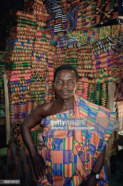 A Kente cloth seller stands in front of his stock in a market in Accra Ghana November 1996