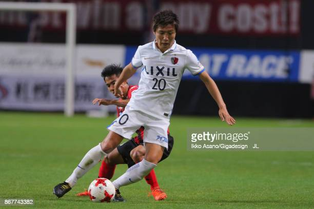 Kento Misao of Kashima Antlers controls the ball under pressure of Chanathip Songkrasin of Consadole Sappporo during the JLeague J1 match between...