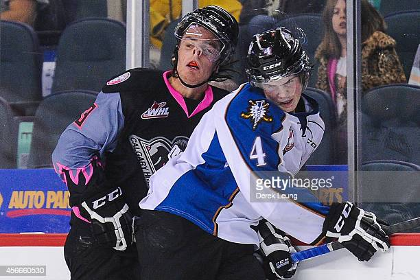Kenton Helgesen of the Calgary Hitmen gets checked by Cale Fleury of the Kootenay Ice during a WHL game at Scotiabank Saddledome on October 4 2014 in...