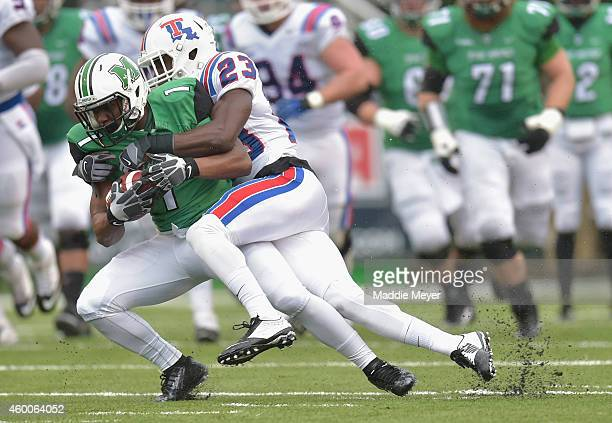 Kentrell Brice of the Louisiana Tech Bulldogs tackles Tommy Shuler of the Marshall Thundering Herd during the first quarter at Joan C Edwards Stadium...