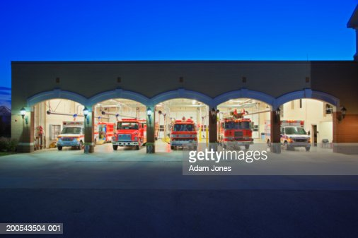 USA, Kentucky, fire engines and ambulances in fire station at dusk