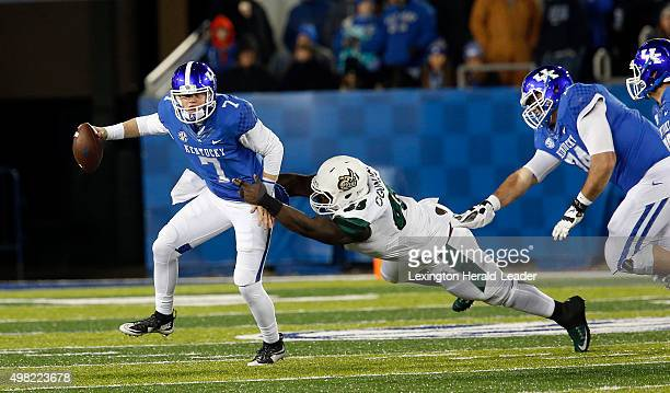 Kentucky quarterback Drew Barker escapes the grasp of Charlotte defensive lineman Larry Ogunjobi on a scramble for a gain in the second quarter at...