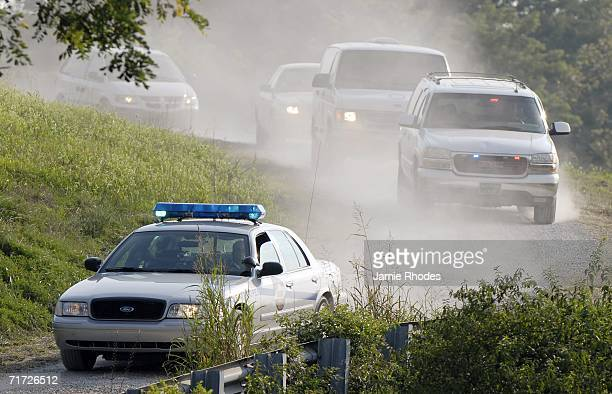 Kentucky State Police cruiser leads a caravan including a LexingtonFayette County Coroner's van away from scene where Comair Flight 5191 crashed...