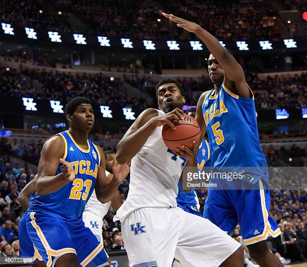 Kentucky Wildcats center Dakari Johnson is defended by UCLA Bruins forward Kevon Looney and UCLA Bruins forward Tony Parker during the first half of...