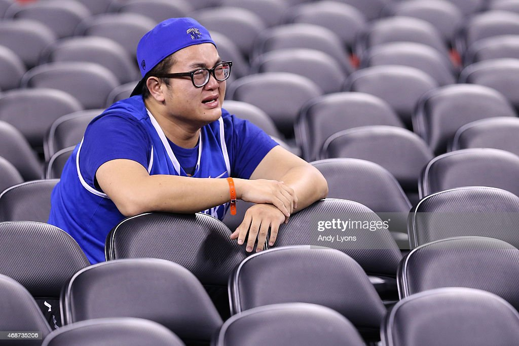 A Kentucky Wildcats fan reacts in the stands after being defeated by the Wisconsin Badgers during the NCAA Men's Final Four Semifinal at Lucas Oil Stadium on April 4, 2015 in Indianapolis, Indiana. Wisconsin defeated Kentucky 71-64.