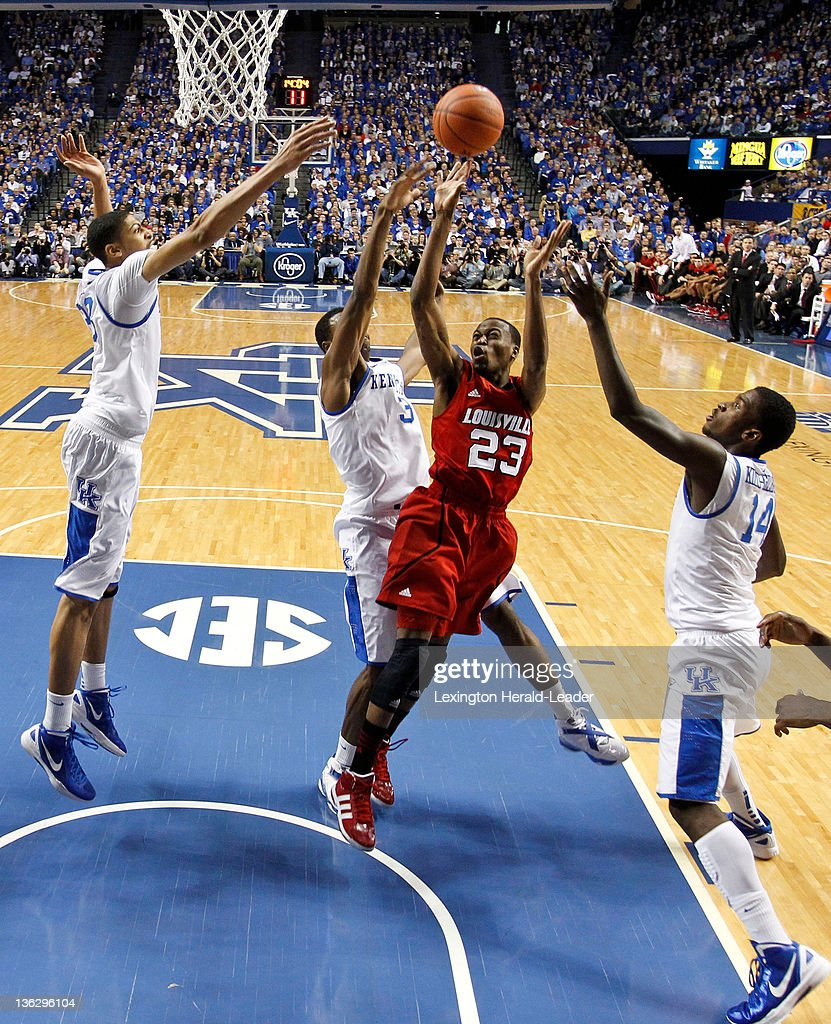 Kentucky Wildcats forward Anthony Davis goes in to block the shot of Louisville Cardinals guard Kevin Ware as he drove into the Kentucky defense...