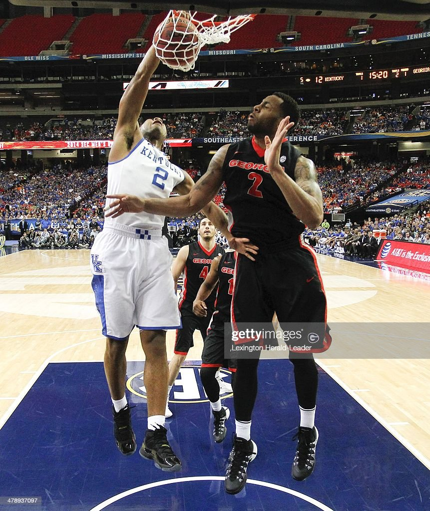 Kentucky Wildcats guard Aaron Harrison dunks over Georgia Bulldogs forward Marcus Thornton for two of his 22 points in the semifinals of the SEC...