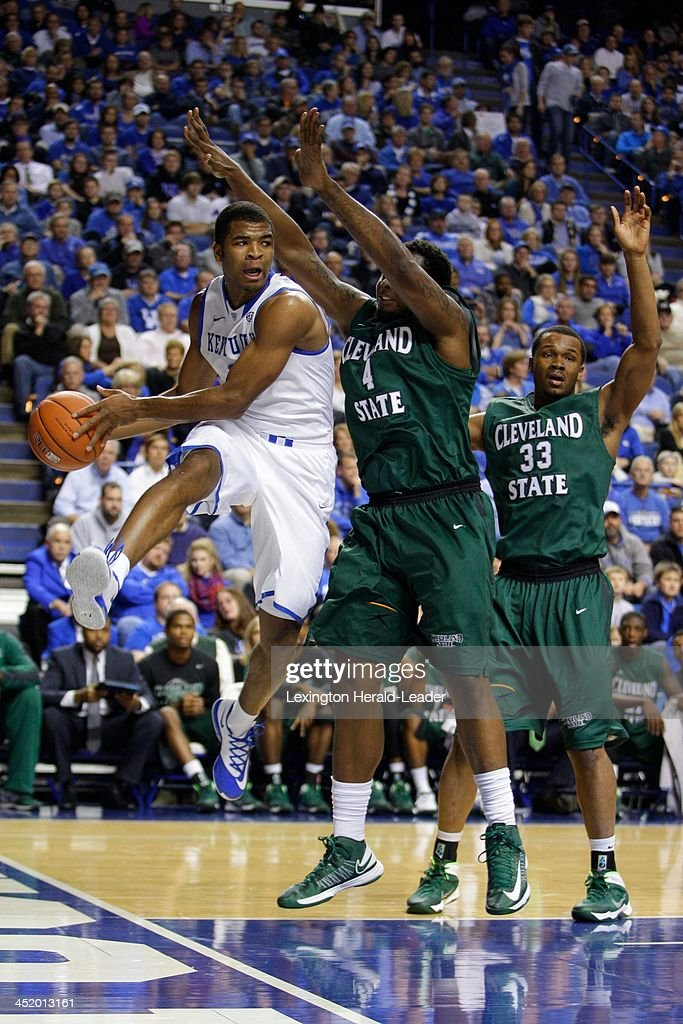 Kentucky Wildcats guard Aaron Harrison left passes around Cleveland State Vikings center Devon Long center during the first half at Rupp Arena in...