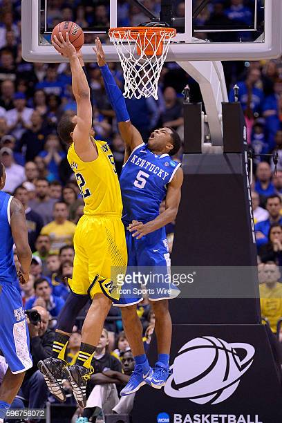 Kentucky Wildcats guard Andrew Harrison battles with Michigan Wolverines forward Jordan Morgan in action during the Div I Men's Championship Elite...