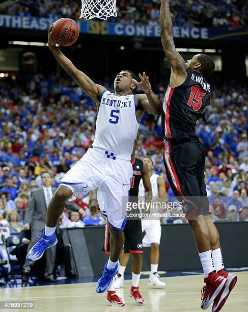 Kentucky Wildcats guard Andrew Harrison drives around Georgia Bulldogs forward Donte' Williams for two of his 12 points during a semifinal in the SEC...