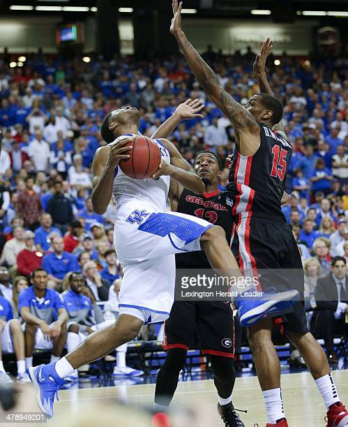 Kentucky Wildcats guard Andrew Harrison gets fouled hard by Georgia Bulldogs forward Donte' Williams and Kenny Gaines during the semifinals of the...