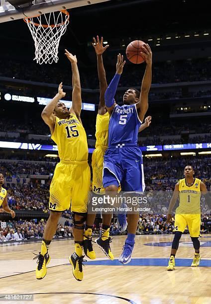 Kentucky Wildcats guard Andrew Harrison scored on a drive past Michigan Wolverines forward Jon Horford and Michigan Wolverines guard Caris LeVert...