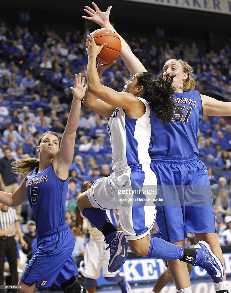 Kentucky Wildcats guard Jennifer O'Neill (0) drives to the basket against DePaul Blue Demons guard Anna Martin (5) and DePaul forward Katherine Harry (51) during game action at Rupp Arena in Lexington, Kentucky, Friday, December 7, 2012. Kentucky defeated DePaul, 96-64.