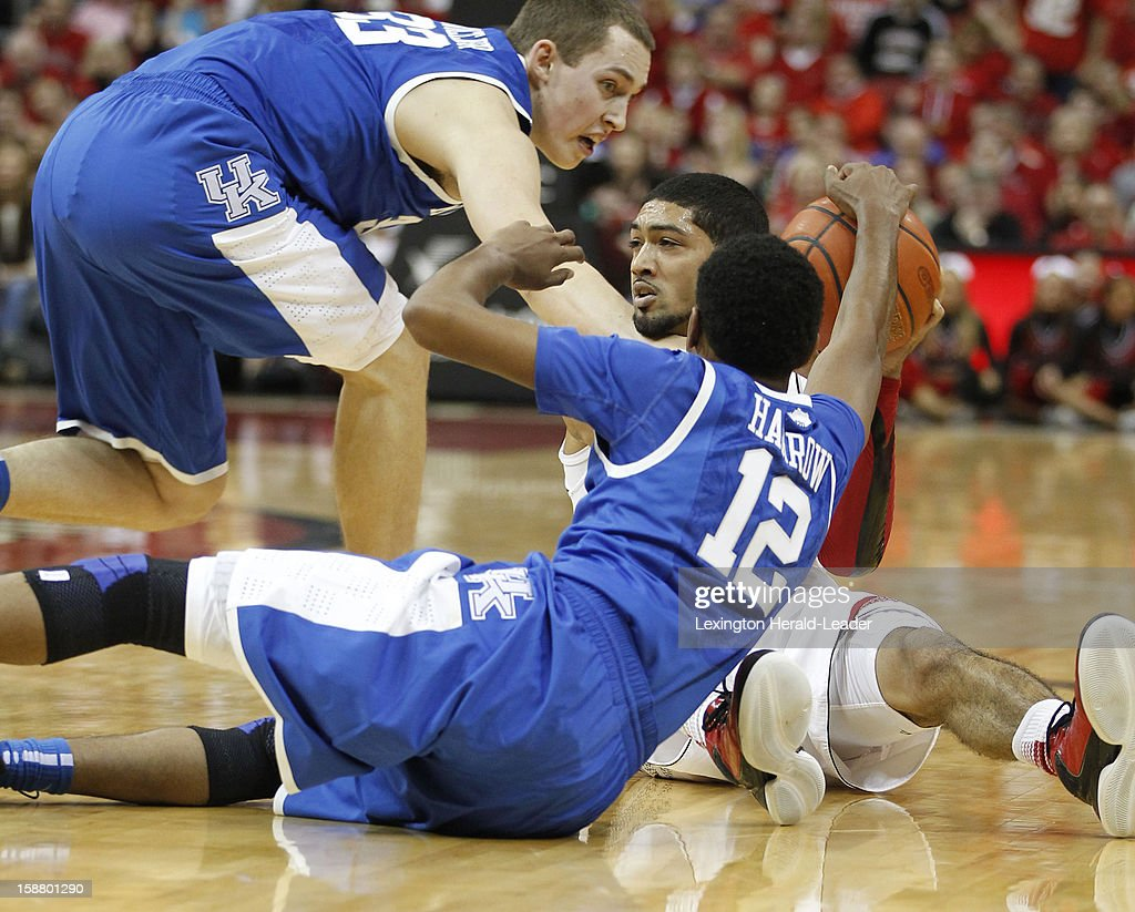 Kentucky Wildcats guard Ryan Harrow (12) and forward Kyle Wiltjer (33) go to the floor with Louisville Cardinals guard Peyton Siva (3) during game action at the KFC Yum! Cente in Louisville, Kentucky, Saturday, December 29, 2012. Louisville defeated Kentucky, 80-77.