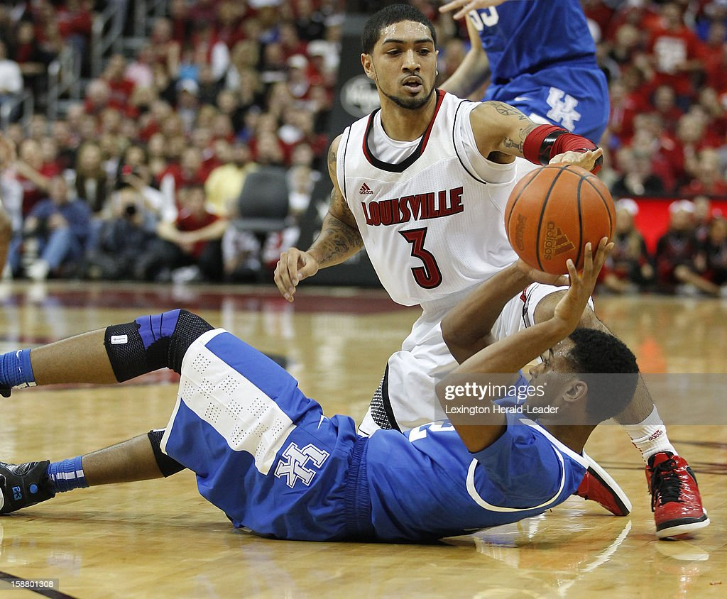 Kentucky Wildcats guard Ryan Harrow (12) passes from his back out of the pressure of Louisville Cardinals guard Peyton Siva (3) during game action at the KFC Yum! Cente in Louisville, Kentucky, Saturday, December 29, 2012. Louisville defeated Kentucky, 80-77.