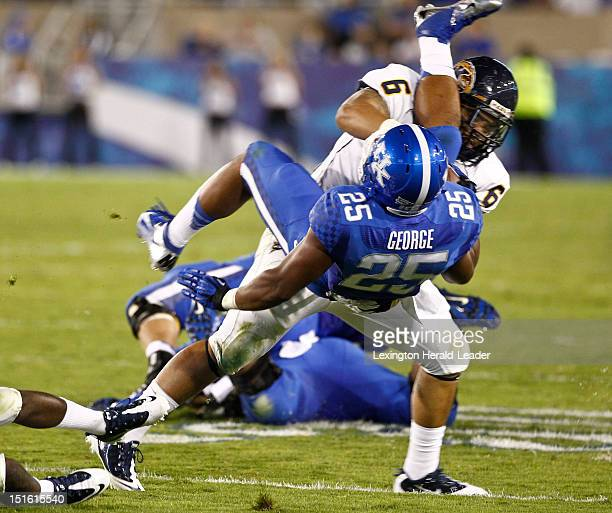 Kentucky Wildcats running back Jonathan George takes a hit from Kent State Golden Flashes defensive lineman Dana Brown Jr during game action in...