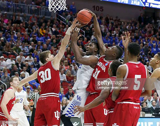 Kentucky's Alex Poythress middle has his shot blocked by Indiana's Collin Hartman and Thomas Bryant during firsthalf action in the second round of...