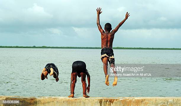 Kenya, Lamu archipelago, Lamu, 3 friends jumping into the water