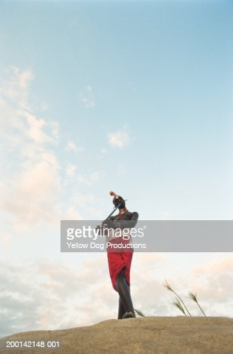 Kenya, Masai Mara, Samburu man playing reed flute on rock, low angle