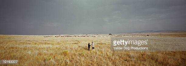 Kenya, Masai Mara, two businessmen shaking hands in field
