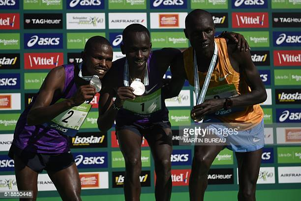 Kenyan athletes Laban Korir Cyprian Kotut and Stephen Chemlany pose with their medal on the podium after competing in the 40th Paris Marathon on...