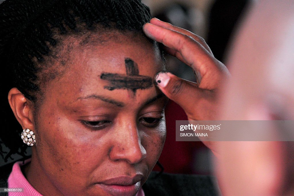 A Kenyan Catholic faithful applies ash during a Lent mass on February 10, 2016 at the Holy family Basilicah in Nairobi. Lent takes place from February 10 till March 26, 2016 and is a solemn observance in the liturgical year of many Christian denominations, lasting for a period of approximately six weeks leading up to Easter Sunday. / AFP / SIMON MAINA