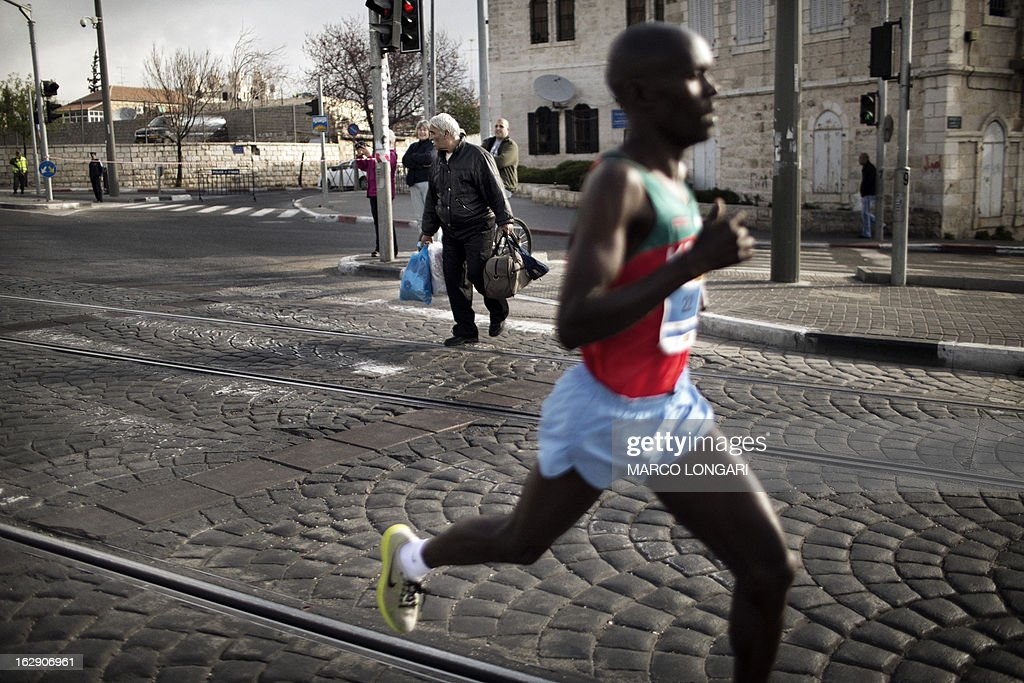 A Kenyan competitor takes part in Jerusalem's third annual marathon as a man crosses a street on March 1, 2013. About 20,000 runners took part in Jerusalem's third annual marathon, with 1,000 police deployed to provide security along the route, police said.