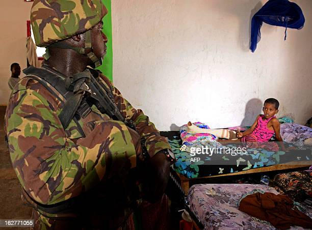 A Kenyan Defence Forces soldier stands guard at a clinic in Kismayo Somalia on February 26 2013 Recent clashes broke out between rival progovernment...